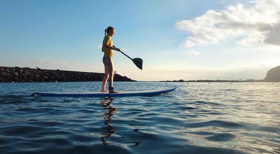 tavola surf sup in acqua con ragazza che rema